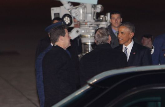 Kansas Governor Sam Brownback (r) (left) greeting President Obama as he arrives in Topeka aboard Air Force One the night before his speech in Lawrence at the University of Kansas.