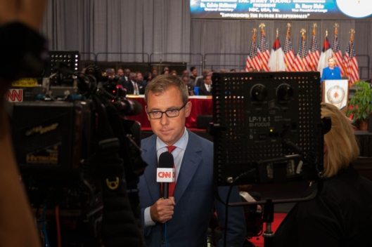 A CNN crew (reporter, producer, cameraman) doing a stand up from the front row of the press riser while Hillary Clinton was speaking at the National Baptist Convention in Kansas City - September 8, 2016.